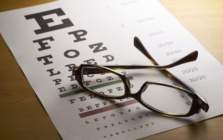 Eye Exam Chart on table with aPair Of Glasses